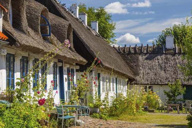 Cycle past thatched-roof houses