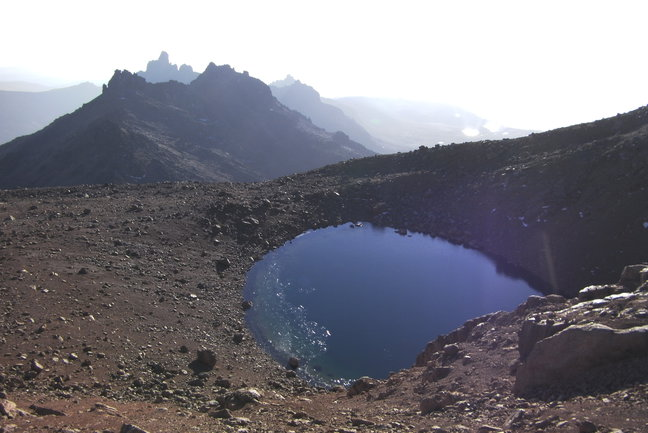 Harris Tarn, high on Mt Kenya, catches the suns first rays. Behind are the spires of Terere and Sendeo.